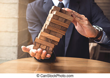 Alternative risk concept, plan and strategy in business, Young intelligent businessman raise the wood game, hands of executive sustain wood block on the tower, Collaborative management