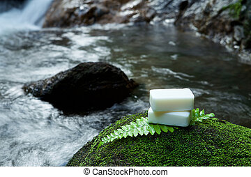 Alternative skin care homemade soap on stone, green leaf with tropical waterfall in the background. as a spa concept.
