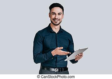 altijd klaar, om te, help., mooi, jonge man, in, hemd, wijzende, op, zijn, digitaal tablet, en, het glimlachen, terwijl, staand, tegen, grijze , achtergrond