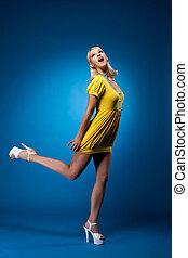 alto, donna, in, giallo, sexy, vestire, salto, su, blu