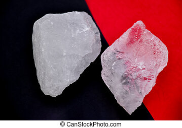 Two alum cubes are placed on red and black background. Solf and selective focus on rim of alum cube.