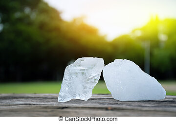 Two cubes of alum on wooden table with blurred background. Soft and selective focus on alum.
