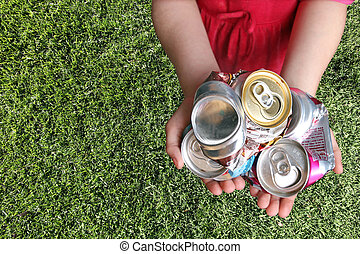 Aluminum Cans Crushed For Recycling in a Childs Hands