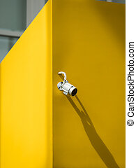 aluminum closed circuit camera for security on the yellow concrete wall