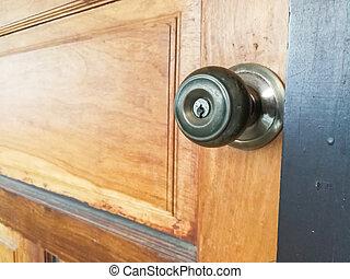 Aluminum door knob on the brown wood door