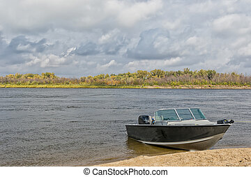 Aluminum motor boat moored in sandy shore rapid river