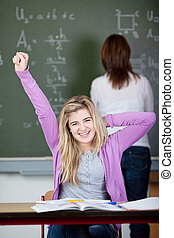 aluno feminino, esticar, escrivaninha, com, professor, em, fundo