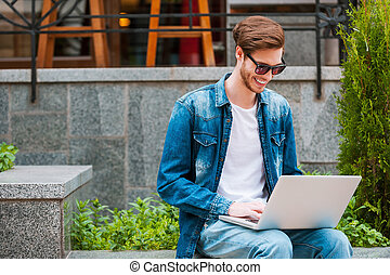 Always connected. Smiling young man working on laptop while sitting outdoors