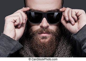 Always in style. Portrait of handsome young bearded man adjusting his sunglasses and looking at camera while standing against grey background