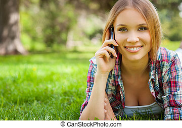 Always in touch. Beautiful young woman talking on the mobile phone and smiling while lying on the grass in park
