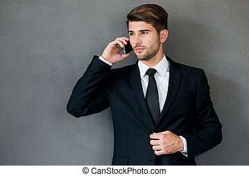 Always in touch. Confident young businessman talking on mobile phone while standing against grey background