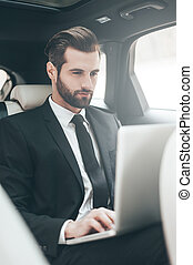 Always in touch. Handsome young businessman working on his laptop while sitting in the car