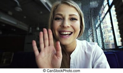 Always in touch with her friends. Cheerful young beautiful woman waving saying hi while looking at camera and sitting at her working place