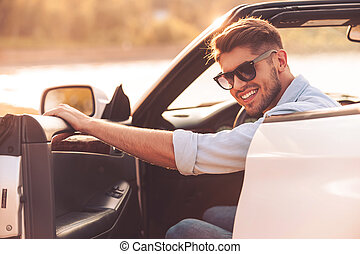 Always ready for good driving. Cheerful young man smiling at camera and closing the door while sitting inside of his white convertible