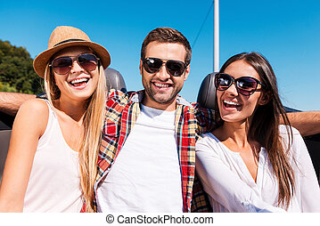 Always ready to have some fun. Three young happy people looking at camera and smiling while enjoying road trip in convertible