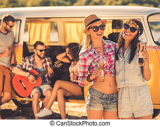 Always together and never apart. Two cheerful young women holding bottles of beer while their friends sitting at the background in retro minivan