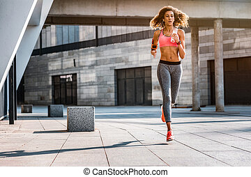 Nice fit woman running with a bottle of water