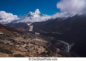Ama Dablam summit or peak and Nepalese village in Himalayas