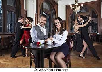 amaestrado, sentado, pareja, bailarines, tango, mientras, tabla, sonriente
