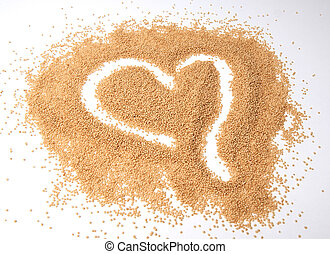 Amaranth seeds in a heart shape isolated on white background.