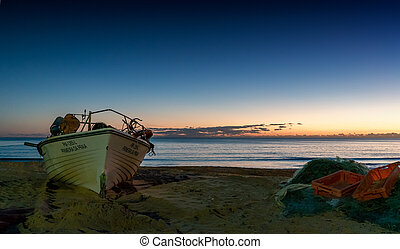 sunset at the Praia do Pescadores on the Algarve coast of Portugal with a small fishing boat on the beach