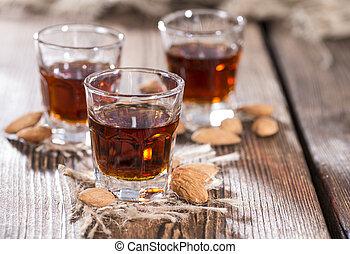 Amaretto Shot on dark wooden background with some almonds