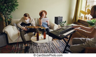 Amateur band is rehearsing in home studio singing and playing guitar and keyboard using microphone and musical equipment. Beer bottles and snacks are visible.