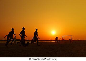 amateur football at beach during sunset