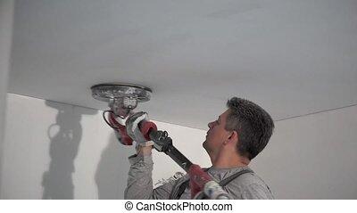 Amateur man polishing home ceiling with sanding grinder...
