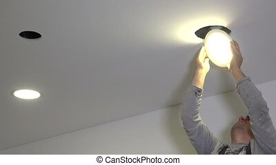amateur man replace led light panel. Lamp start to illuminate bright. Do it yourself. Static shot.