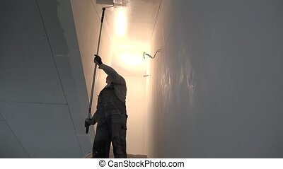 Amateur man with roller tool paint ceiling of staircase in...