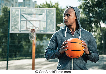 Serious young man looking at the basketball court