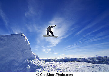 Amateur snowboarder making a grab in big air jump in...