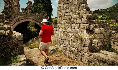 Amateur traveler wearing red tshirt explores ancient...