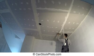 Amateur worker apply plaster on ceiling joints. Do it yourself timelapse