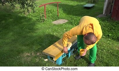 amateur worker painting wood surface with brush in yellow...