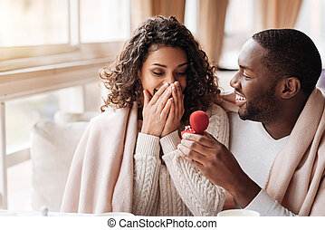 Amazed African American couple getting engaged in the cafe