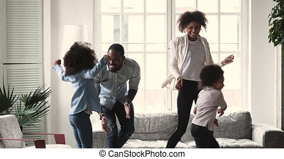 Amazed african american family dancing to music at home.