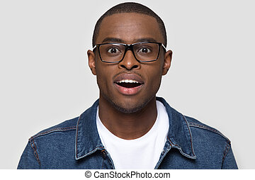 Amazed african man wearing glasses looking at camera