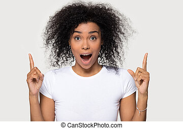 Amazed african woman pointing finger up looking at camera