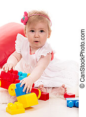 Amazed baby girl playing with toys