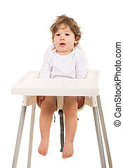 Amazed boy standing straight in chair