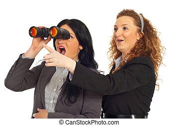 Amazed business women looking in binocular - Two very...