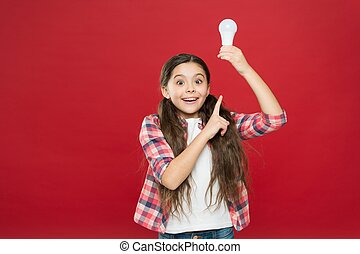 amazed child girl pointing finger on lamp bulb with light, inspiration