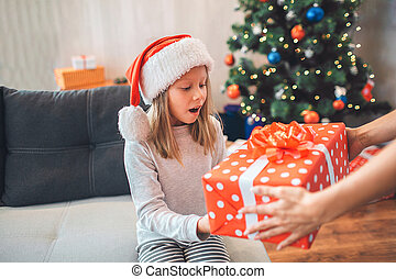 Amazed child holds present and looks at it. She keeps mouth opened. Girl wears Christmas hat. Adult supports her by holding present with hands. They are in decorated room.