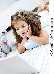 Amazed child - Portrait of lovely girl looking at laptop...