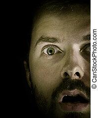 Amazed! - Close-up portrait of amazed guy in the dark