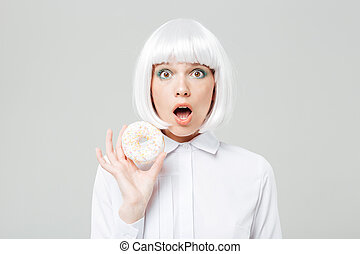 Amazed cute young woman in blonde wig holding donut - Amazed...