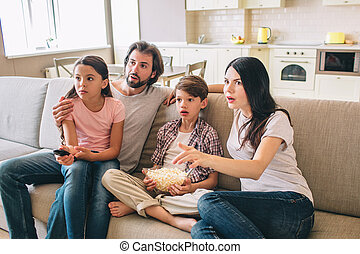 Amazed family sits on sofa and watches TV. They look amazed. Girl sits on daddy's lap. Boy has bowl of popcorn. Woman eats this food.