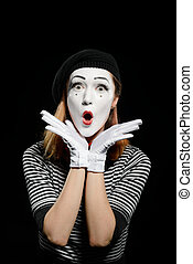 Amazed female mime on black. Vertical portrait of pantomime actress